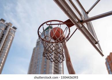 Basketball ball hits the basket outdoor, nobody