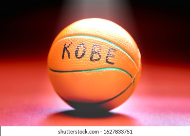 Basketball ball with KOBE inscription, red background. Famous basketball player concept. Ray of light on basketball ball.