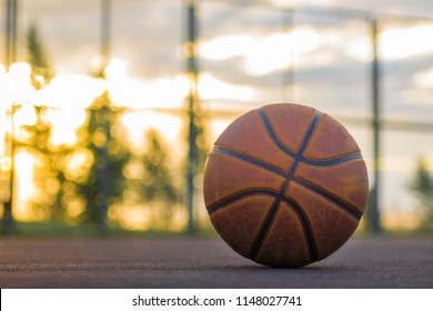 Basketball ball lies on the ground against the background of the evening sky. Sports background