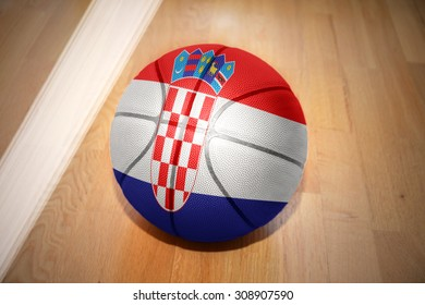 basketball ball with the national flag of croatia lying on the floor near the white line