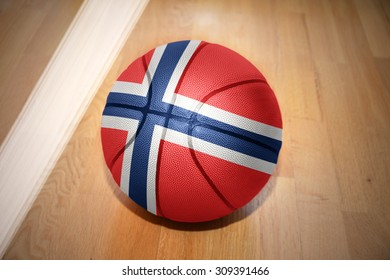 basketball ball with the national flag of norway lying on the floor near the white line