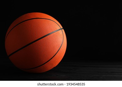 Basketball ball on black wooden table against dark background, space for text