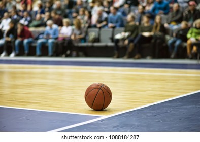 The basketball ball is on the basketball court. Fans sit in the stands in the background