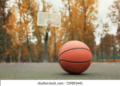 basketball ball on the outdoors court with hoop on the background. Sport equipment