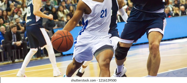 The basketball ball is on the basketball player's hand