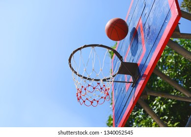 Basketball ball over ball hoop in basketball court outdoor.