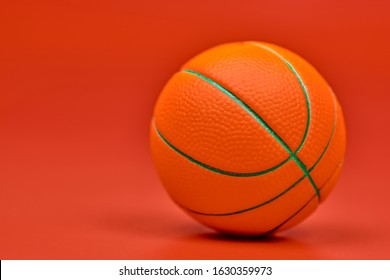 Basketball ball, red background, copy space. Spherical ball used in basketball games