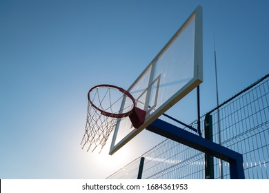 basketball basket against the blue sky in the sun, minimalistic picture, diagonals, rhythm