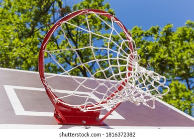Basketball basket installed on a basketball backboard on the outdoor sports field, bottom view against the trees branches and sky