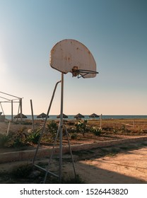 Basketball board in the beach right in sunset with bungalows in the background and a clear blue sky