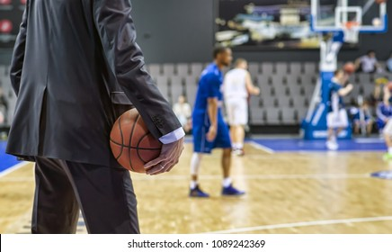Basketball coach holds the ball in his hand