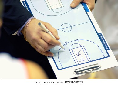 Basketball coach write tactics on coaching board