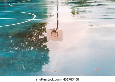 Basketball court after rain. Basketball half-court line. Outdoor court wet with rain. Court with reflective water. Tree and sun reflection on water. Abstract art. Minimal design. Abstract design.