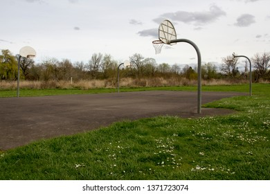 Basketball court in a community park with blooming wild flowers in the foreground during springtime.