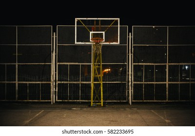The basketball court during night, view on basketball hoop and fence.