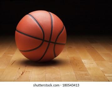 A basketball with a dark background on a hardwood gym floor