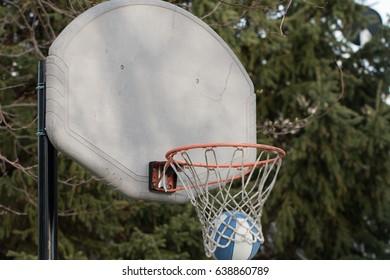 Basketball falling through worn hoop