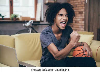 Basketball fan. Cheerful young African man watching TV and holding basketball ball while gesturing on the couch at home