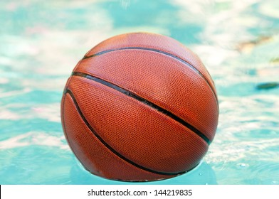 Basketball floating in swimming pool water.