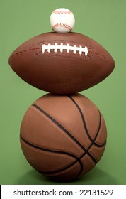 A basketball, football and baseball balance on top of each other