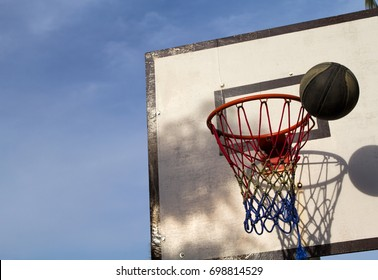 Basketball game outdoor equipment contrast photo. Missed ball throw in basket. Street basketball. School holiday contest. Basketball competition victory. Basketball game on summer. Active playing