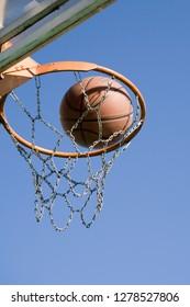 Basketball goalpost and blue sky.