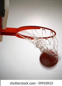 Basketball going into hoop and net with white background