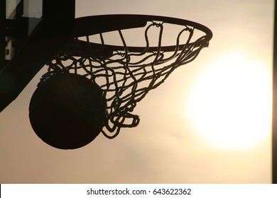 Basketball Going into Hoop Outdoors Late in the Afternoon in Silhouette against Yellow Sky Backlit by the Setting Sun
