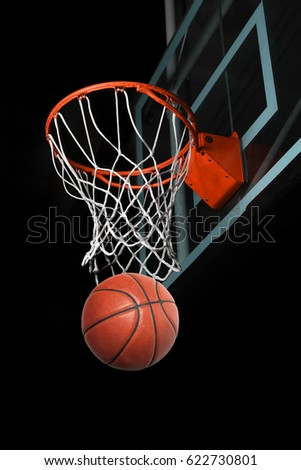 Basketball going through hoop isolated over black background