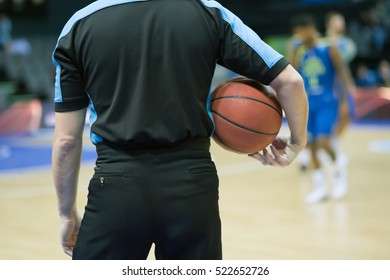 Basketball is in the hands of the referee. In the background are team players A basketball rests on the court at halftime.