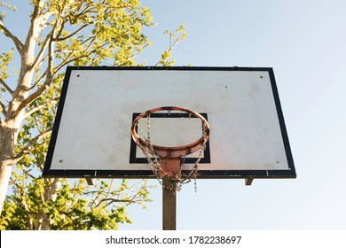 Basketball hoop against a blue sky in sunny day - Vintage basketball hoop with a backboard - Metal basketball hoop - Lifestyle object for sport on the street city - Concept of reaching the goal