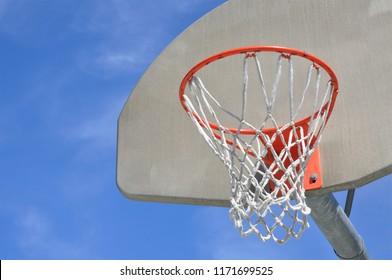 Basketball hoop against a bright blue sky.