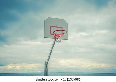 Basketball hoop against a cloudy sky in a Park on the beach