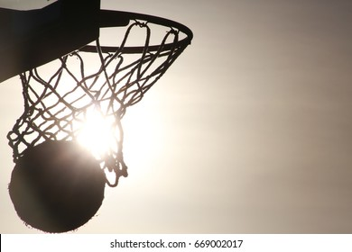Basketball Hoop, Backboard and Net with Ball Swishing Through in Silhouette with Setting Sun Gleaming Through Directly Behind at Quiet Waters Park, Deerfield Beach, Florida
