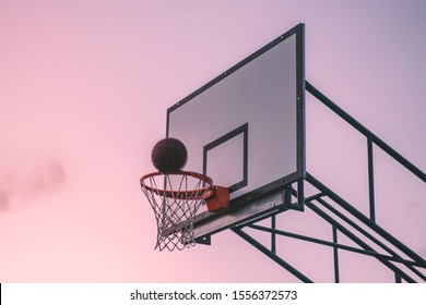 Basketball hoop with ball scoring going through at sunset sky. Basketball board isolated
