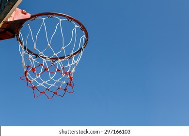 Basketball hoop with blue sky background.