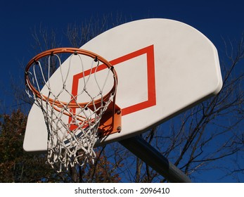 A basketball hoop extending out into a bright blue sky