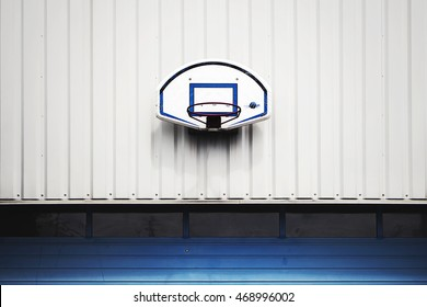 Basketball hoop fixed on a white wall above the blue garage door