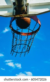 A basketball hoop with a basketball. The basketball is going in the hoop. The hoop has a double rim and a chain net. It's shot from below with the sky as a background.