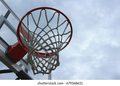 Basketball Hoop with net on the background of cloudy sky. Basketball in cloudy weather.