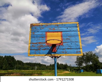Basketball hoop on an old wooden backboard, which is installed in the open air. Close-up of a sports facility.