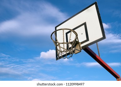 Basketball hoop outdoors with blue sky and light clouds