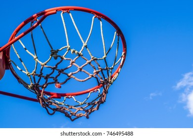 Basketball hoop outdoors, closeup, low angle view. Red basketball hoop viewed from below against blue sky.