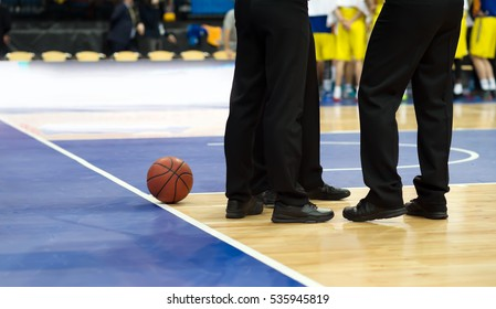 A basketball lies on the basketball court about three referee at halftime. In the background are players on the basketball team