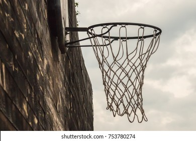 Basketball net on a street wooden wall on a sky background close.