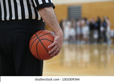 basketball official holds ball during timeout