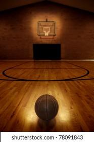 Basketball on floor of empty basketball court