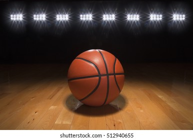 A basketball on a wood floor beneath bright arena lights