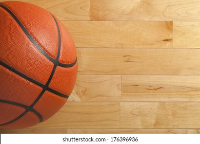 A basketball on a wood gym floor viewed from above