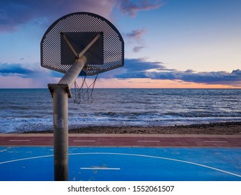 Basketball play court near the sea, cloudy sky at sunset.